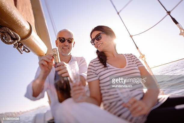 Mature couple with celebratory champagne on a sunset yacht cruis