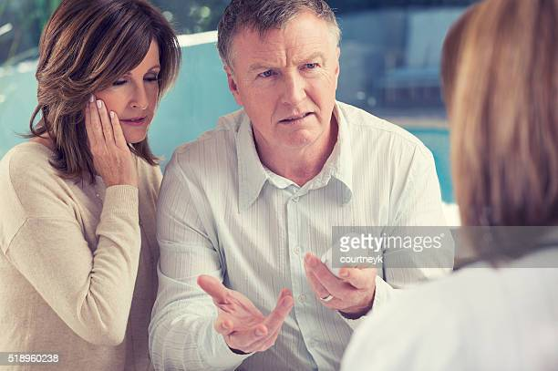 Mature couple with doctor and medicine