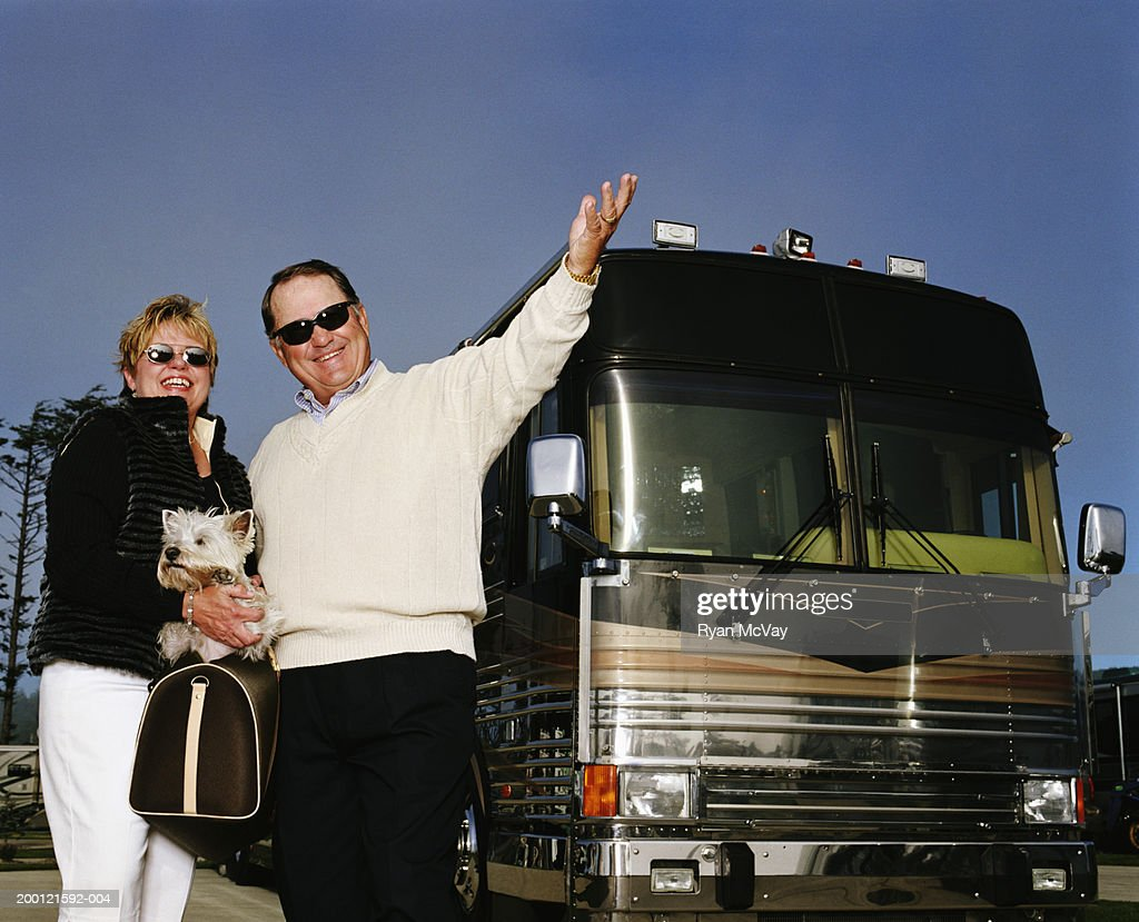 Mature couple with dog standing beside coach bus, smiling, portrait : Stock Photo