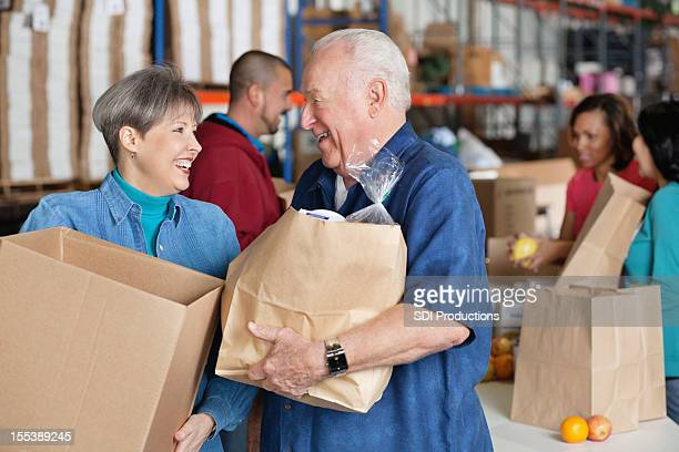 Mature couple with donations at food bank donation center