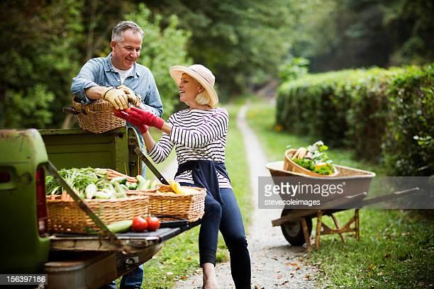 Älteres Paar mit geerntetes Gemüse im Garten.
