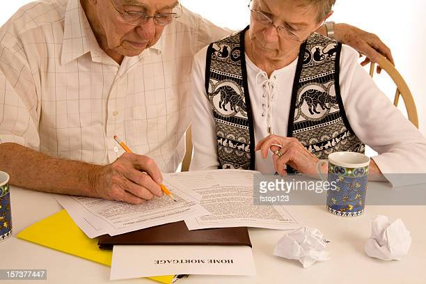 Mature couple with mortgage loan paperwork.