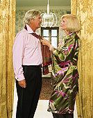 Mature couple woman pulling scarf around man's neck