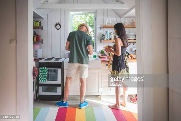Mature couple working in kitchen seen from doorway at home
