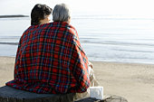A Mature Couple Wrapped up in a Blanket Together, Rear View, Three Quarter Length