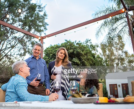 Mature couples chatting at garden party table