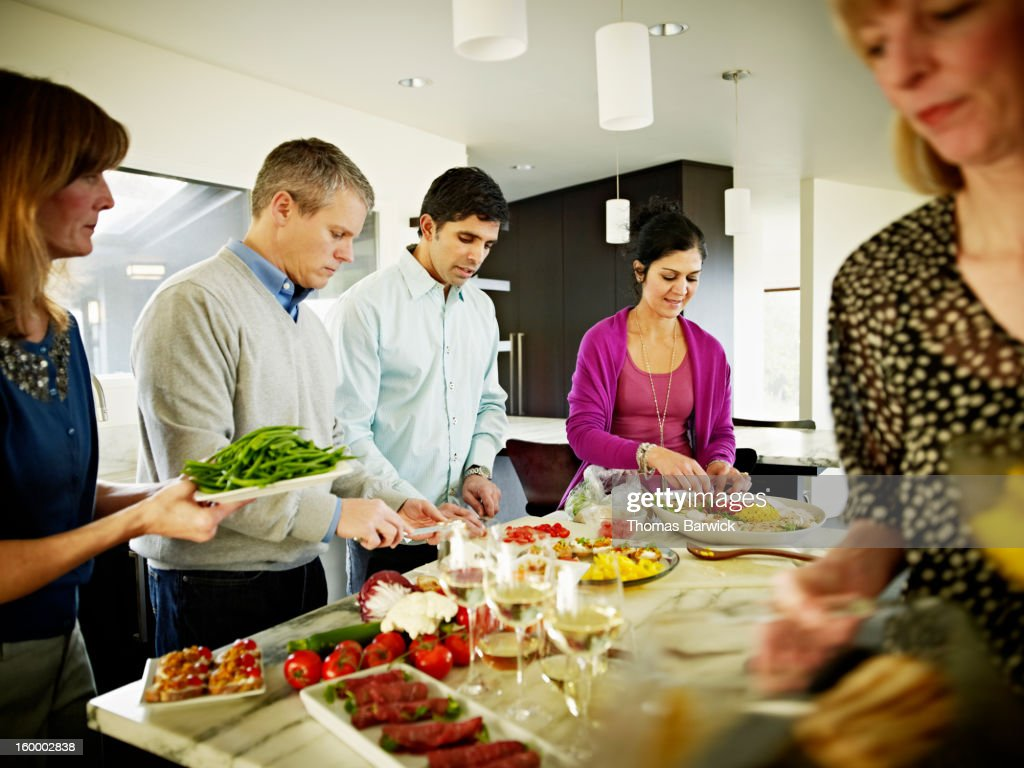 Mature couples preparing food in home kitchen : Stock Photo