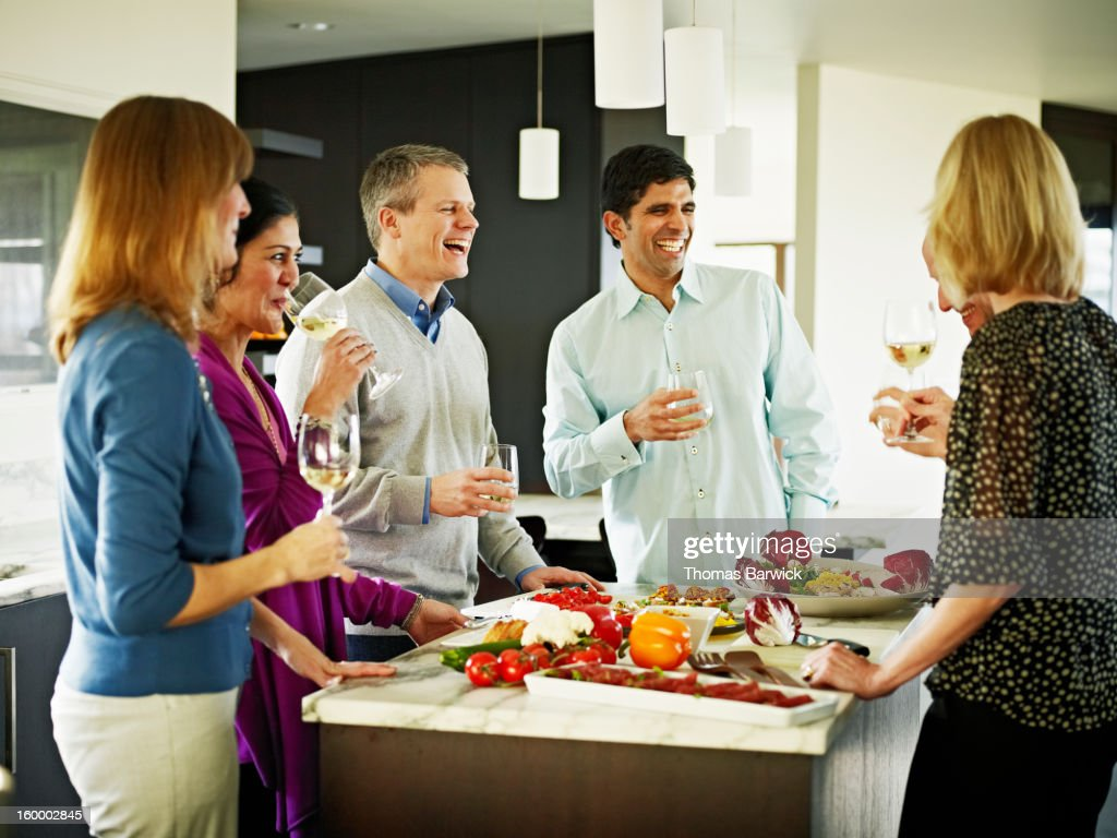 Mature couples preparing meal in home kitchen : Stock Photo