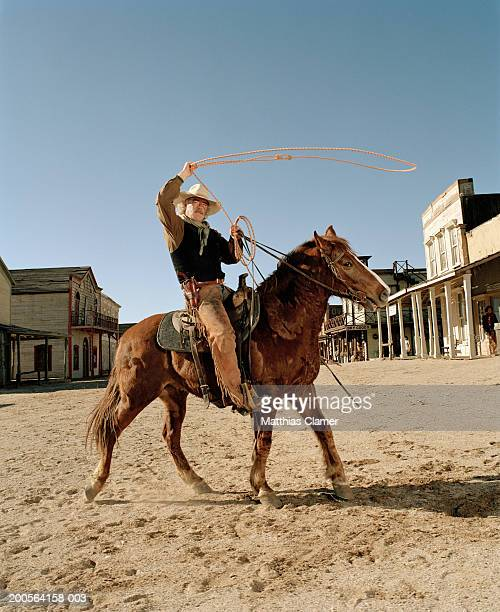 Mature cowboy riding horse and lassoing