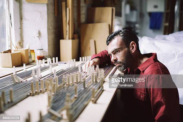 Mature craftsman checking organ pipes in pipe organ workshop
