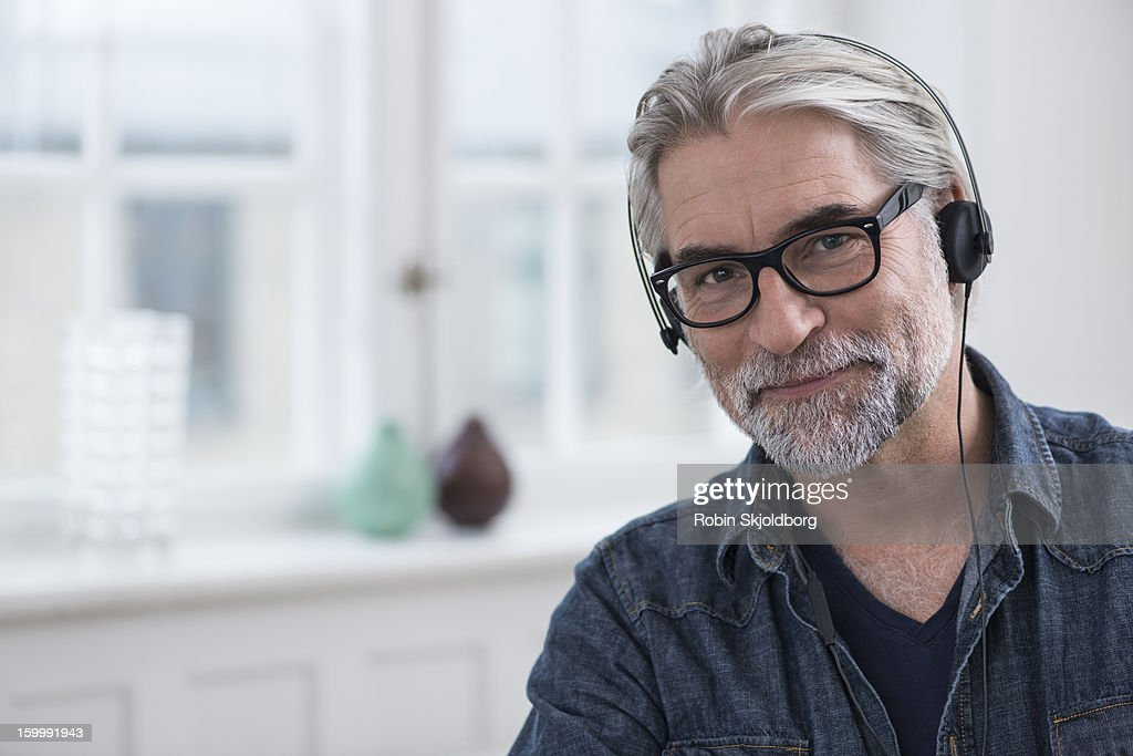 Mature creative Man smiling with headset : Stock Photo