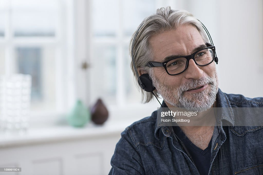 Mature creative man wearing headset, smiling : Stock Photo