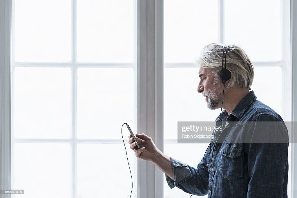 Mature creative man with mobile and headset : Stock Photo