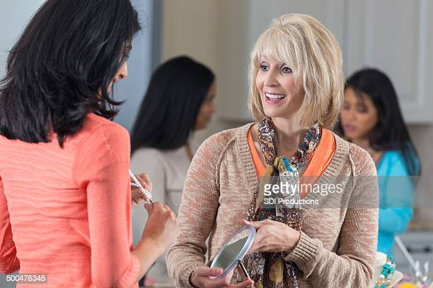 Mature customer service representative selling jewelry at home party
