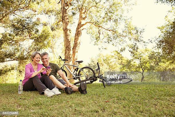 Mature cycling couple sitting in park looking at smartphone
