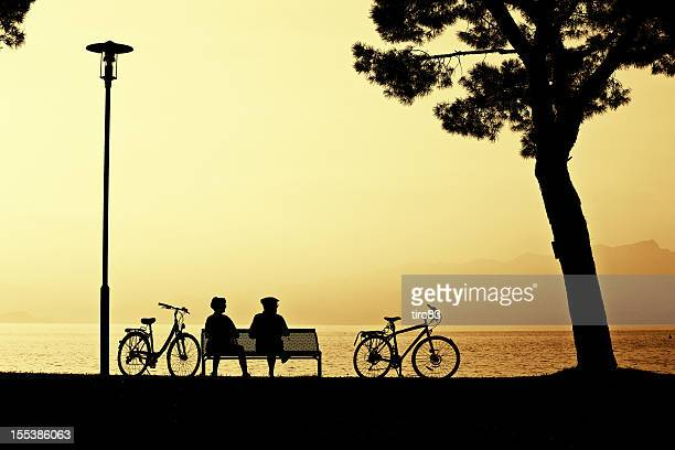 Mature ciclisti su seashore Panchina al tramonto