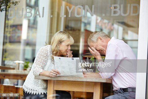 Mature dating couple giggling at restaurant table : Stock Photo
