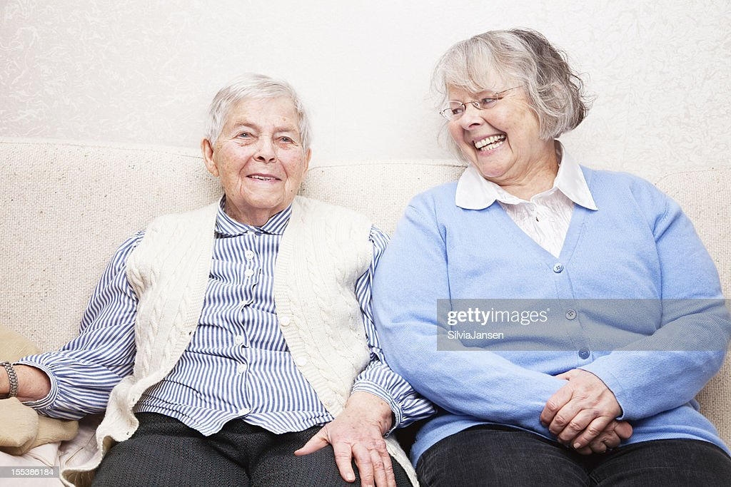 Mature daughter and senior mother on sofa