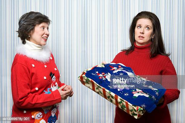 Mature daugther receiving Christmas sweater gift from mother, studio shot
