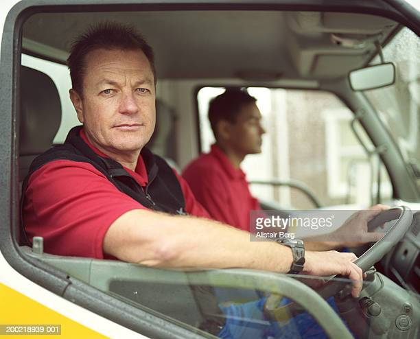 Mature delivery man at wheel of truck with colleague, portrait