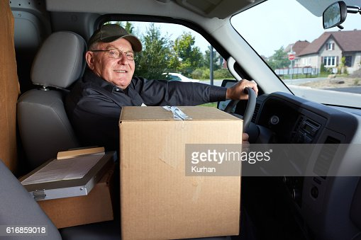 Mature delivery man with a parcel. : Stock Photo