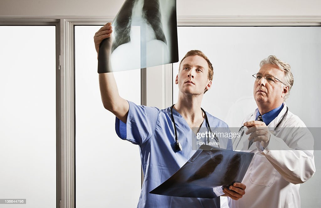 Mature doctor and resident examining chest x-rays : Stock Photo