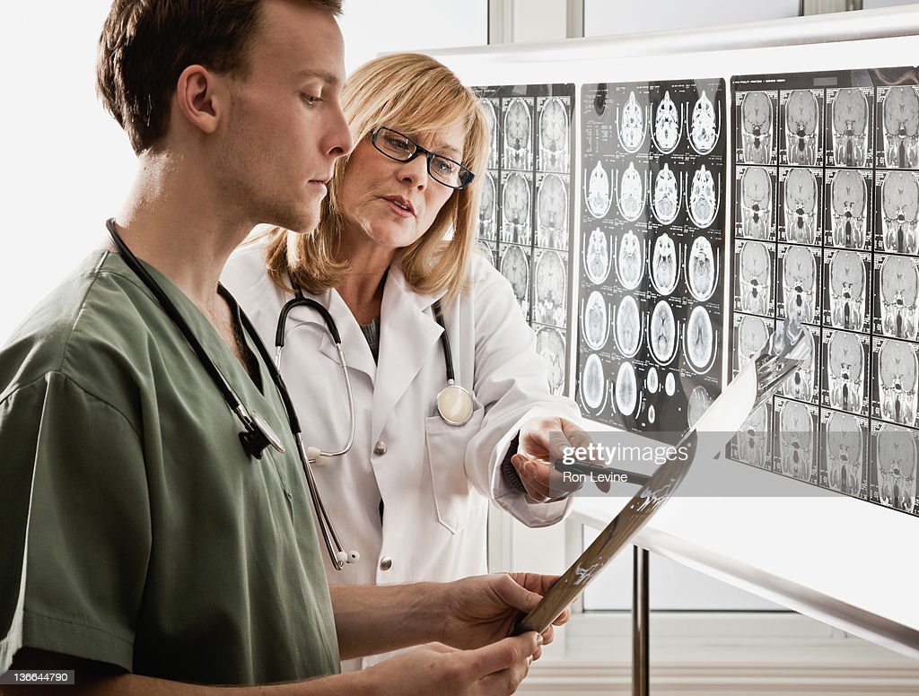 Mature doctor and resident examining mri's : Stock Photo