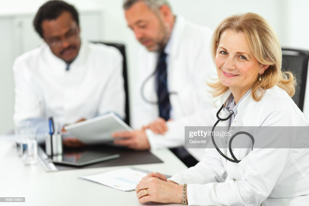Mature doctor at meeting : Stock Photo