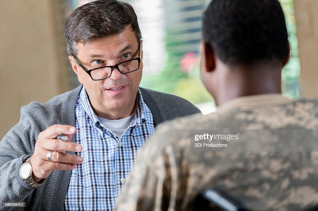 Mature doctor counseling young soldier during therapy session