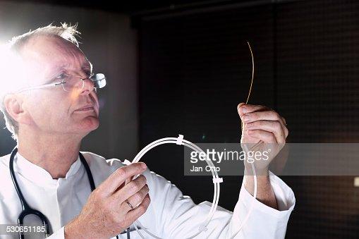 Mature doctor demonstrating catheter