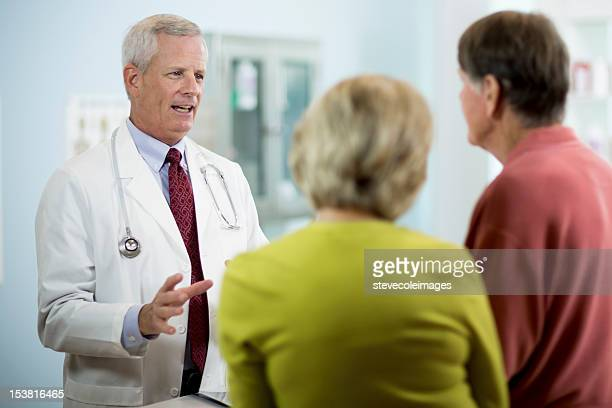 Mature Doctor Explaining Medical Results To Couple.
