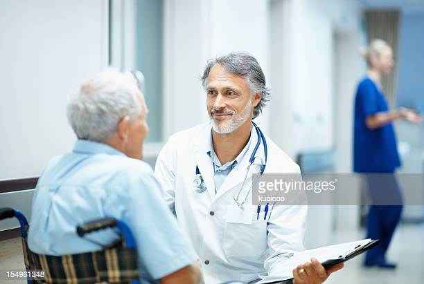 Mature doctor explaining reports to a handicapped man
