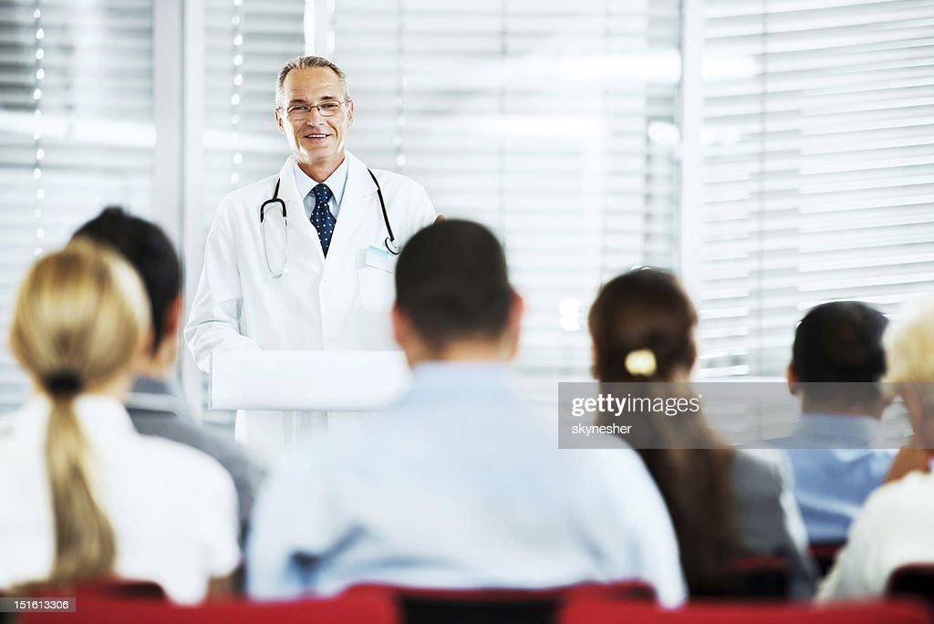 Mature doctor giving a speech on  seminar.