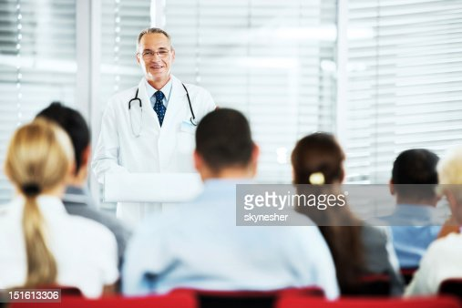 Mature doctor giving a speech on  seminar.