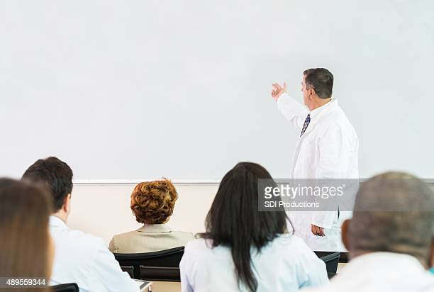 Mature doctor giving lecture during healthcare conference or lecture