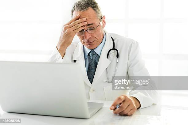 Mature doctor holding his head in pain.