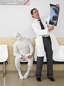 Mature doctor looking at x ray with bandaged patient