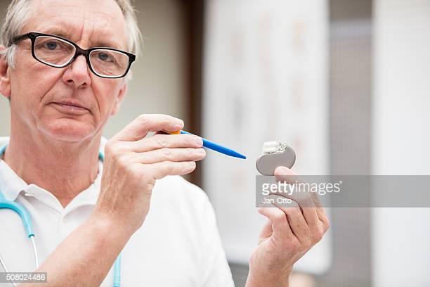 Reife Arzt zeigt auf Kardiale Herzschrittmacher