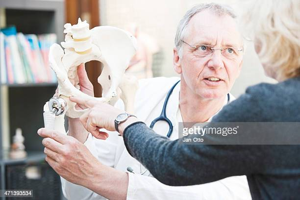 Mature doctor presenting total hip arthroplasty to female patient