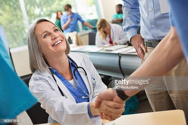 Mature doctor welcoming college medical student to seminar or class
