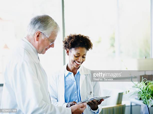 Mature doctors comparing notes on digital tablets