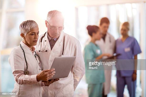 Mature doctors working on laptop in a hospital.