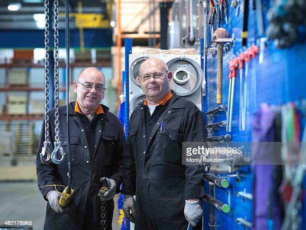 Mature engineers working in engineering factory, portrait