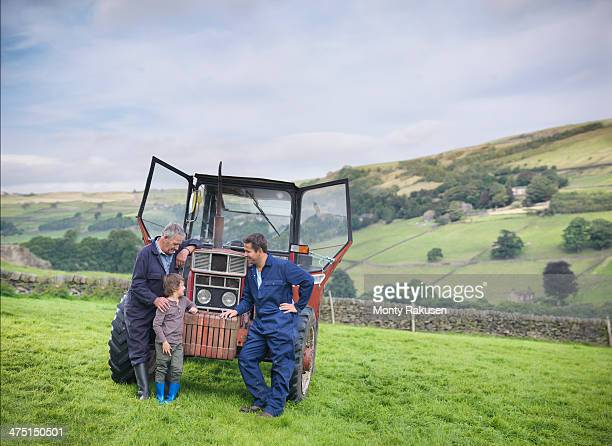 Mature farmer, adult son and grandson next to tractor in field