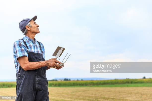 Mature farmer flying a drone over a field