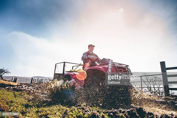 Mature Farmer Riding a Quad Bike