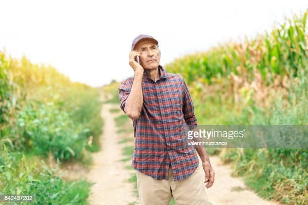 Mature farmer talking on smart phone in field