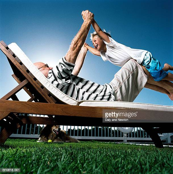 Mature father playing with son (4-6) on sun lounger