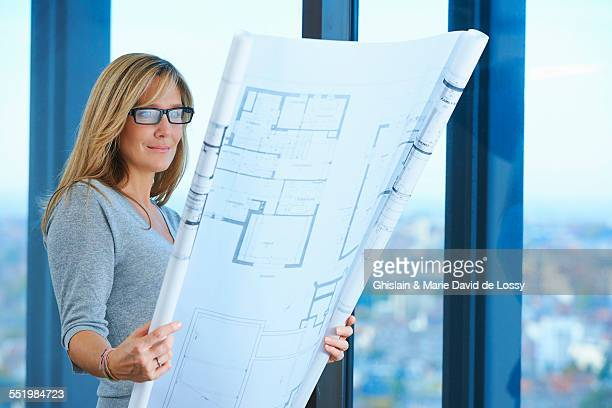 Mature female architect looking at plans in skyscraper office, Brussels, Belgium