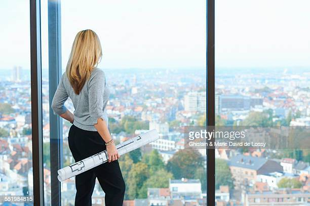 Mature female architect looking from office window at Brussels cityscape, Belgium